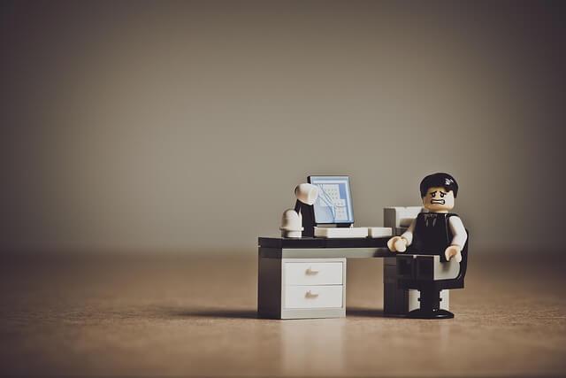 パソコンの前で困る人形の写真
