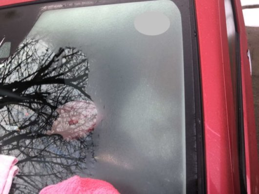 凍ってしまった軽自動車のフロントガラスの写真