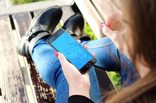 iphoneを持つ女性の写真