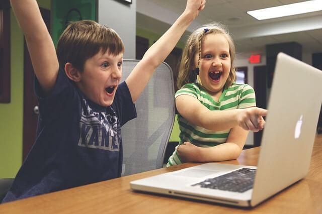 パソコン画面を見て喜ぶ子供